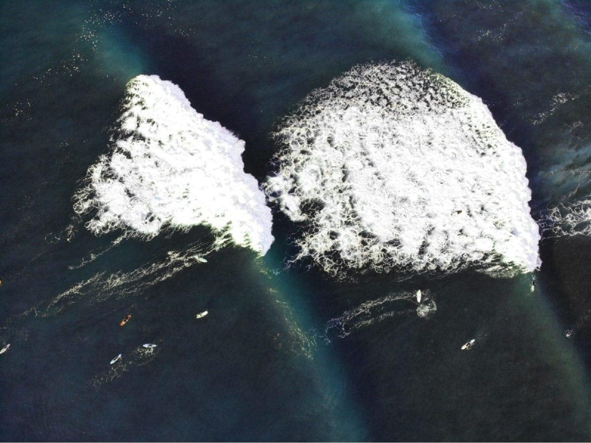 Photographie aérienne de surfeurs entre deux vagues